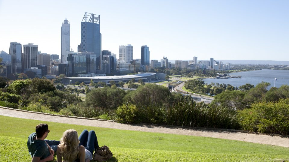 Couple relaxing at Kings Park and Botanical Garden with Perth City Skyline in the background